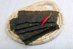 Nori seaweed sheets. Spicy Nori seaweed sheets with pepper on wood stock photography