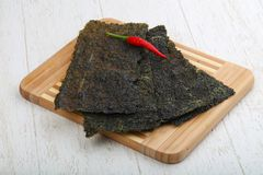 Nori seaweed sheets. Spicy Nori seaweed sheets with pepper on wood stock photos