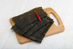 Nori seaweed sheets. Spicy Nori seaweed sheets with pepper on wood royalty free stock image