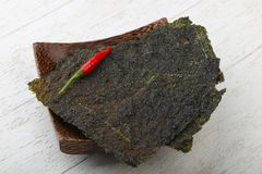 Nori seaweed sheets. Spicy Nori seaweed sheets with pepper on wood royalty free stock photos