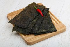 Nori seaweed sheets. Spicy Nori seaweed sheets with pepper on wood royalty free stock images