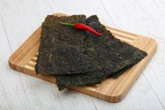 Nori seaweed sheets. Spicy Nori seaweed sheets with pepper on wood stock photo