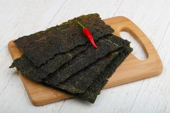 Nori seaweed sheets. Spicy Nori seaweed sheets with pepper on wood royalty free stock photo