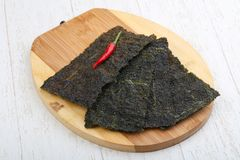 Nori seaweed sheets. Spicy Nori seaweed sheets with pepper on wood royalty free stock photography