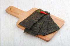 Nori seaweed sheets. Spicy Nori seaweed sheets with pepper on wood stock images