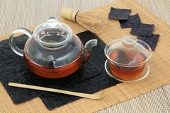 Nori Seaweed Tea. Japanese nori seaweed tea health drink with glass teapot and tea cup, dried sheets, whisk and stirrer on bamboo background. Full of healthy stock image