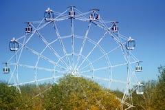 Noria contra el cielo azul y los árboles Imagen de archivo libre de regalías