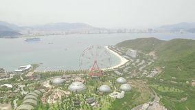 Noria gigante en parque de atracciones en el mar y el paisaje moderno de la ciudad Parque de atracciones con la noria grande en e almacen de video