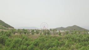 Noria gigante en parque de atracciones en la colina verde y el paisaje del mar Parque de atracciones con la noria grande en el ma metrajes