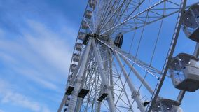 Noria giratoria contra el cielo azul y las nubes: pedazo de estructura entera con las cápsulas de las cabinas y la parte de centr metrajes