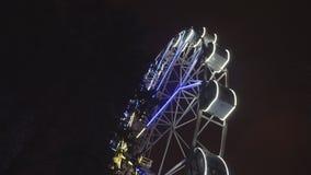 Noria que gira en el parque de atracciones debajo del cielo nocturno oscuro almacen de metraje de vídeo