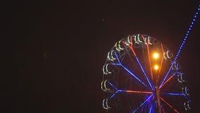 Noria que gira en el parque de atracciones debajo del cielo nocturno oscuro metrajes