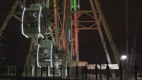 Noria que gira en el parque de atracciones debajo del cielo nocturno oscuro almacen de video
