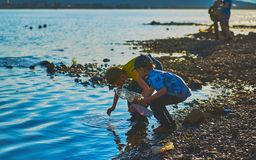 Norilsk Ryssland - Juni 20, 2017: pojkar som spelar på kusten av sjön Royaltyfria Bilder