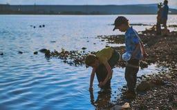 Norilsk Ryssland - Juni 20, 2017: pojkar som spelar på kusten av sjön Fotografering för Bildbyråer