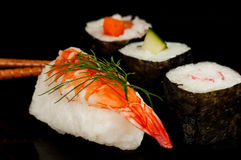 Norimaki and nigiri sushi on black. Norimaki and nigiri sushi.  Prawn, cucumber, pepper and surimi on rice.  On black Royalty Free Stock Photos