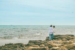 Normala flickor på stranden med deras armar upp Royaltyfria Bilder