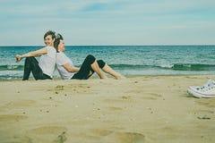 Normala kvinnor på stranden som ler och sitter på sanden Arkivfoto