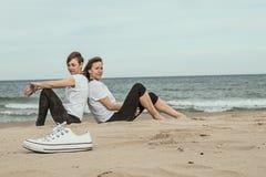 Normala kvinnor på stranden som ler och sitter på sanden Royaltyfri Foto