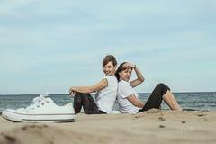 Normale vrouwen op het strand die en op het zand glimlachen zitten Royalty-vrije Stock Foto