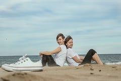 Normale vrouwen op het strand die en op het zand glimlachen zitten Stock Afbeeldingen