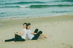 Normale vrouwen op het strand die en op het zand glimlachen zitten Royalty-vrije Stock Afbeeldingen