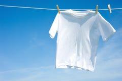 Normales weißes T-Shirt auf einer Wäscheleine Stockfoto