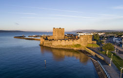 Norman Carrickfergus castle near Belfast. Medieval Norman Castle in Carrickfergus near Belfast, Northern Ireland. Aerial view at sunrise with far view of Belfast Stock Photo