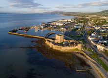 Norman castle in Carrickfergus near Belfast. Medieval Norman Castle in Carrickfergus near Belfast in sunrise light. Aerial view with marina, yachts, parking stock photos