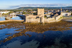 Norman castle in Carrickfergus near Belfast. Medieval Norman Castle in Carrickfergus near Belfast in sunrise light. Aerial view with marina, yachts, parking and Stock Photography