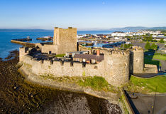 Norman castle in Carrickfergus near Belfast. Medieval Norman Castle in Carrickfergus near Belfast in sunrise light. Aerial view with marina, yachts, parking Stock Photography
