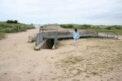 Normandie bunker from World War II with person touring. Lady with black hair has back turned to camera Royalty Free Stock Photo