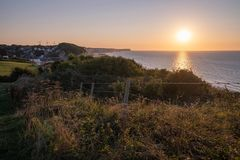 Normandy coast sunset view of cliffs water and grassy hill in France. stock image