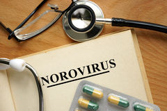 Norovirus. Word Norovirus  on a book and pills Royalty Free Stock Photography