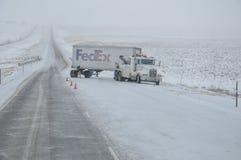 NORR PLATTE, NEBRASKA - FEBRUARI 25, 2010 - som bogserar lastbilen, får klar att dra en Fedex släp ut den iskalla huvudvägen Arkivfoton
