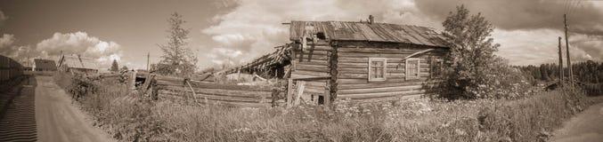 Norr rysk by Isady Sommardag, Emca flod, gamla stugor på kusten, gammal träbro övergiven byggnad Arkivfoto