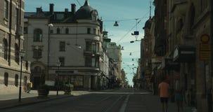 NORRKÃ-PINGEL, ZWEDEN - AUGUSTUS 3, 2018: Een straat met tramsporen in het stadscentrum Het jonge paar lopen stock video