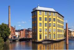 The Strykjarnet building on the Motala River. Norrkoping, Sweden - July 4, 2014: The Industrial Landscape with the Strykjarnet Ironworks, the yellow building in Stock Images
