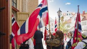 Norrmän framme av kyrkan mellan nationsflaggorna Royaltyfri Bild