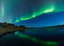 Norrsken i Island ovanför en sjö med fartyget Arkivfoton