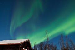 Norrsken (nordliga lampor) över en kabin Royaltyfria Foton