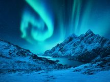 Norrskenet ovanf?r sn?n t?ckte berg royaltyfri bild