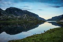 Norsk sjö med dramatisk himmel på solnedgången arkivfoto