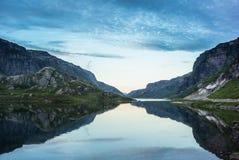 Norsk sjö med dramatisk himmel på solnedgången arkivbild