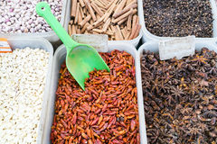 North African red and black spices in containers in a Paris, France market stock images