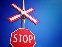 Red stop sign at railway crossing against deep blue sky, North America. royalty free stock images