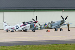 North American P-51 Mustang and Supermarine Spitfire airborne near the hangar Royalty Free Stock Image