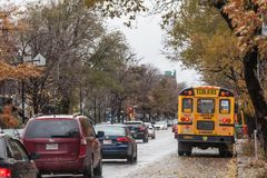 North American Yellow School Bus parked on a street, waiting for students with cars passing by with information in French. MONTREAL, CANADA - NOVEMBER 6, 2018 royalty free stock photos