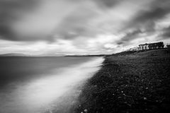 North atlantic ocean landscape in black and white. A fantastic north atlantic landscape on a moody irish day. The town houses overlook the rocky beach and the Royalty Free Stock Images
