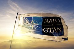 North Atlantic Treaty Organization NATO OTAN logo. flag textile cloth fabric waving on the top sunrise mist fog. Beautiful stock photo